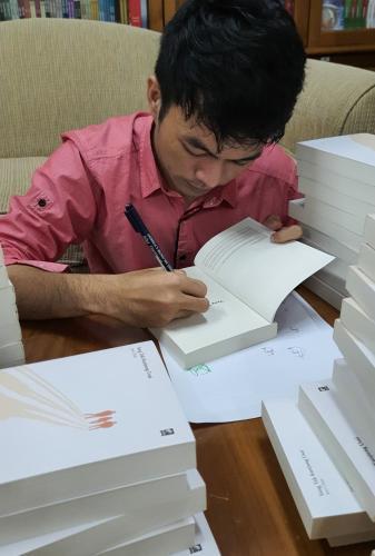 Awi Chin menandatangani novel debutnya, Yang Tak Kunjung Usai di ruang tamu KPG